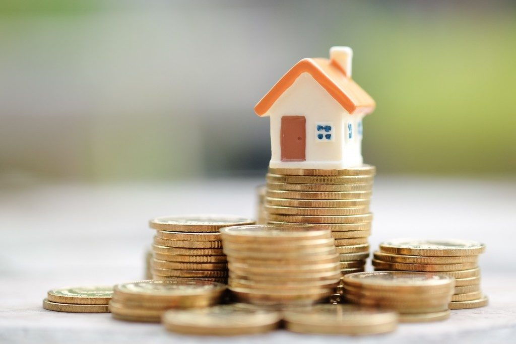 small house on top of coins