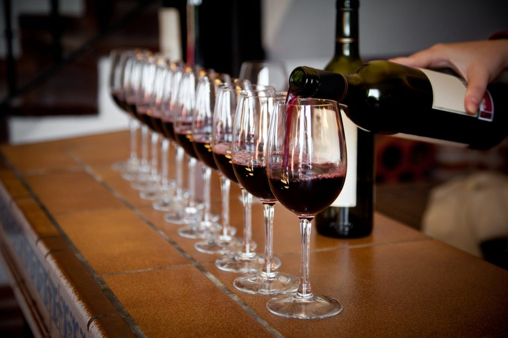 Woman hand with wine bottle pouring a row of glasses for tasting