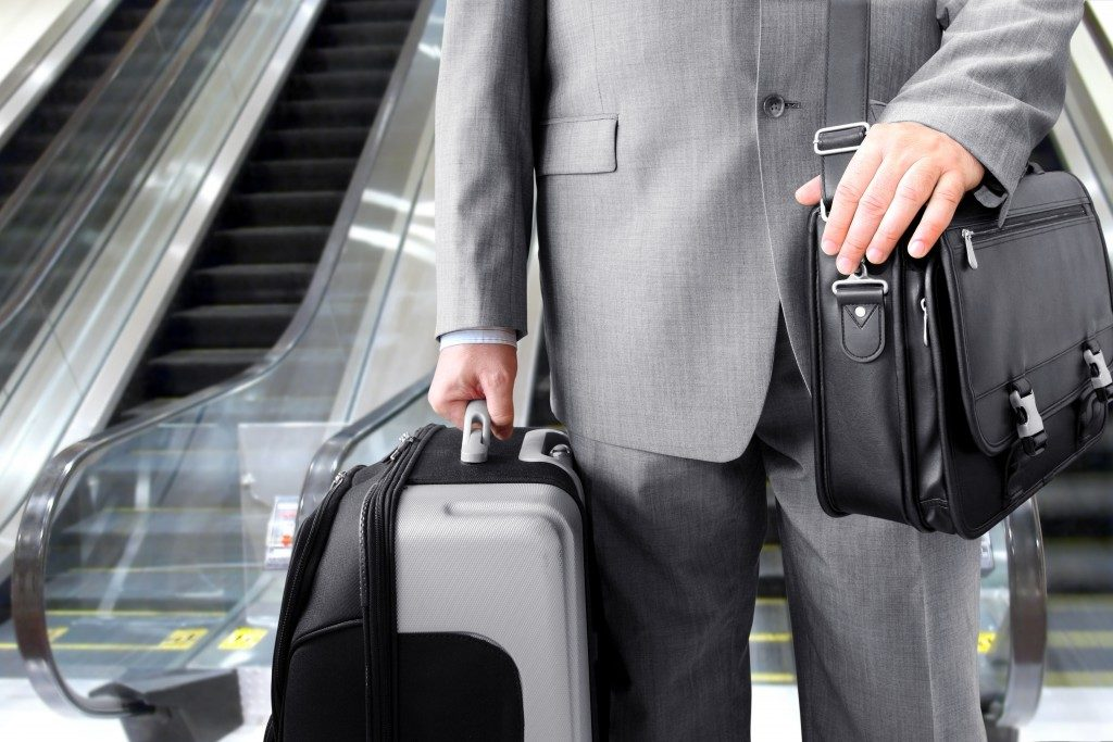 Businessman with his luggage near an escalator at an airport