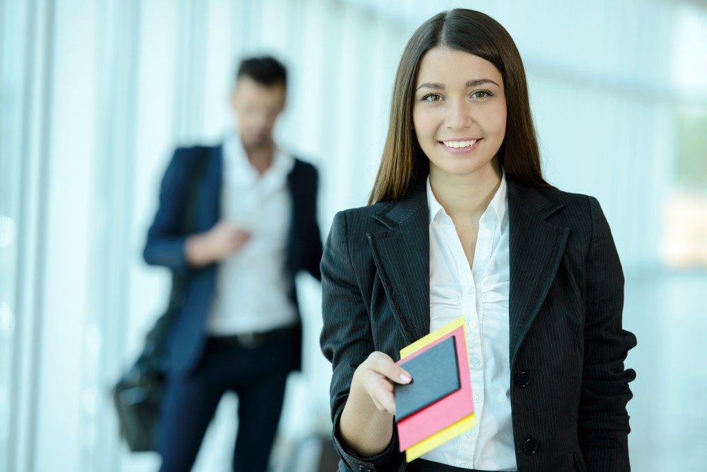 business woman handing over passport at airport check in counter